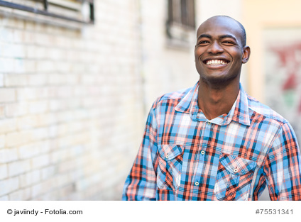Portrait of black man very happy, smiling in urban background