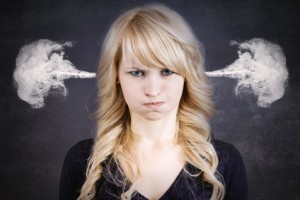 Closeup portrait angry young woman, blowing steam coming out of ears, about to have nervous atomic breakdown, isolated black background. Negative human emotions facial expression feelings attitude