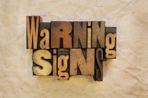 The words Warning Signs written in vintage wood letterpress type