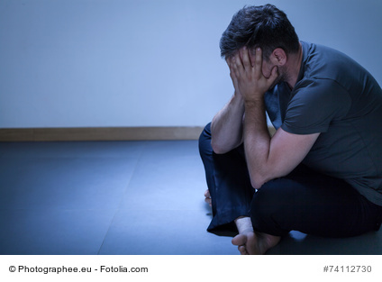 Portrait of lonely depressed man sitting on the floor