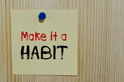 Make it a habit written on paper note over wooden background