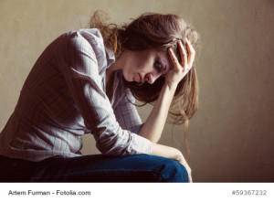 Young sad girl sitting alone in an empty room